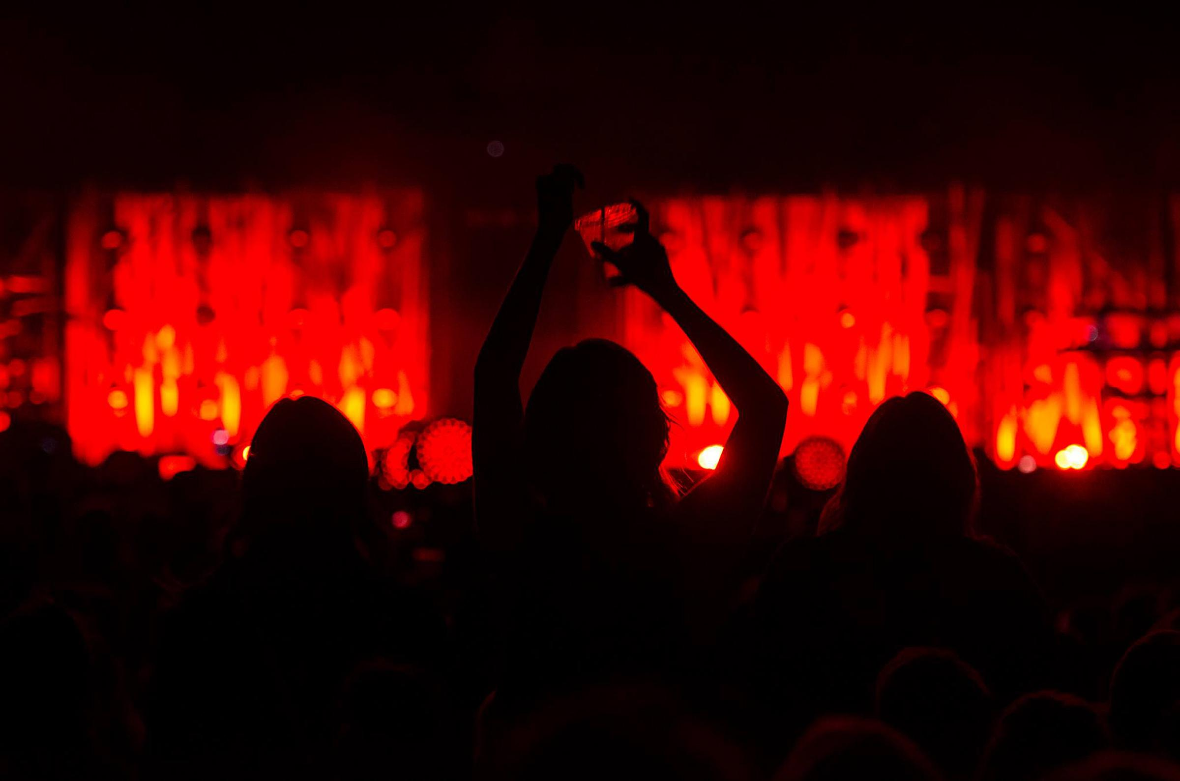 Silhouette of a large crowd of people facing a lighted stage at a concert.