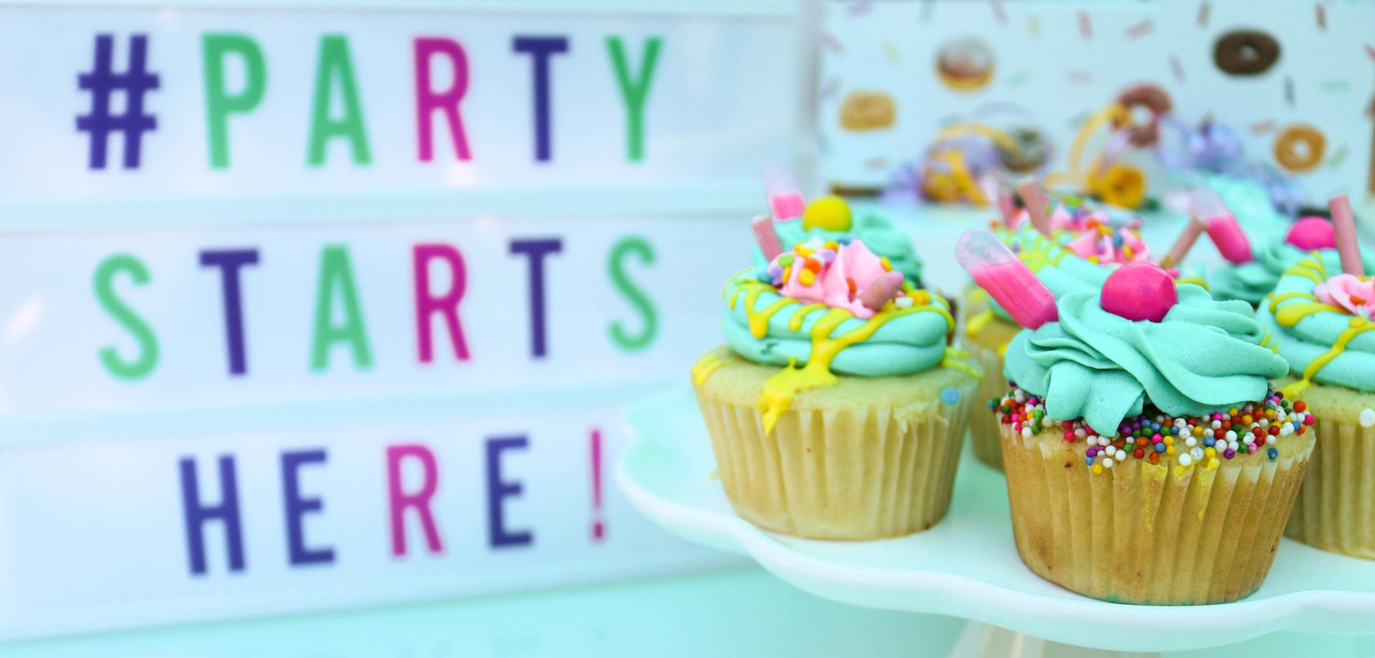 A group of colourful cupcakes on a stand with a sign that reads 'The Party Starts Here!' in the background