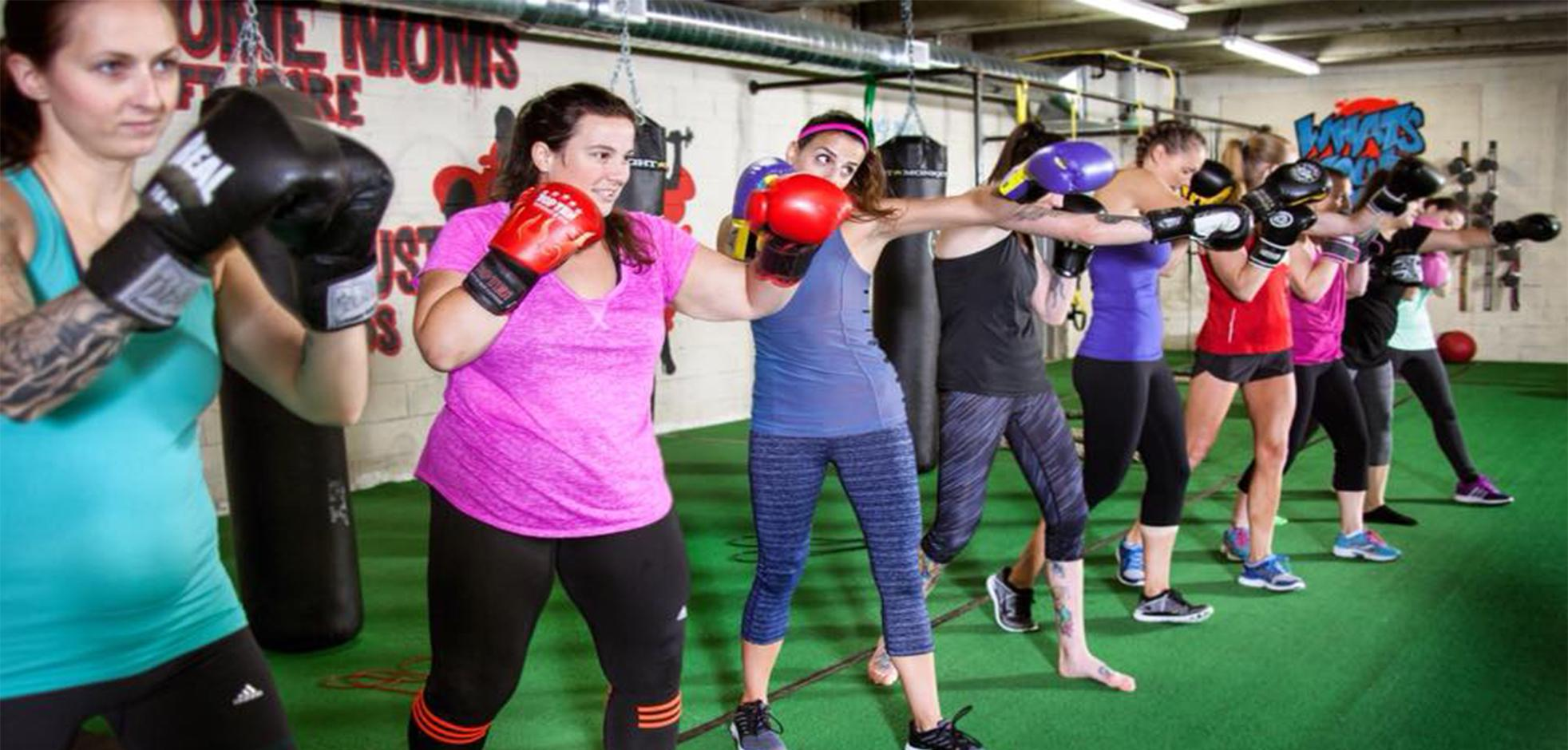 A group of females in a fitness class working out with boxing gloves