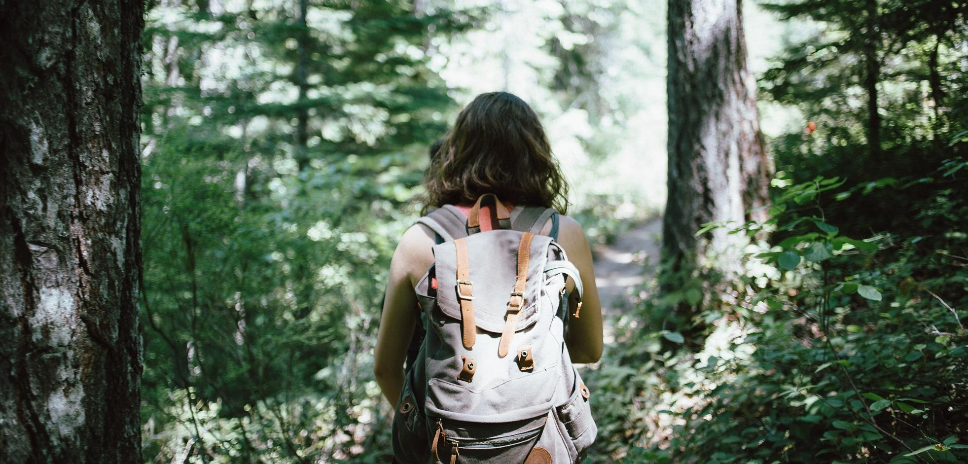 A female with a backpack hiking on a trail in Kains Woods.