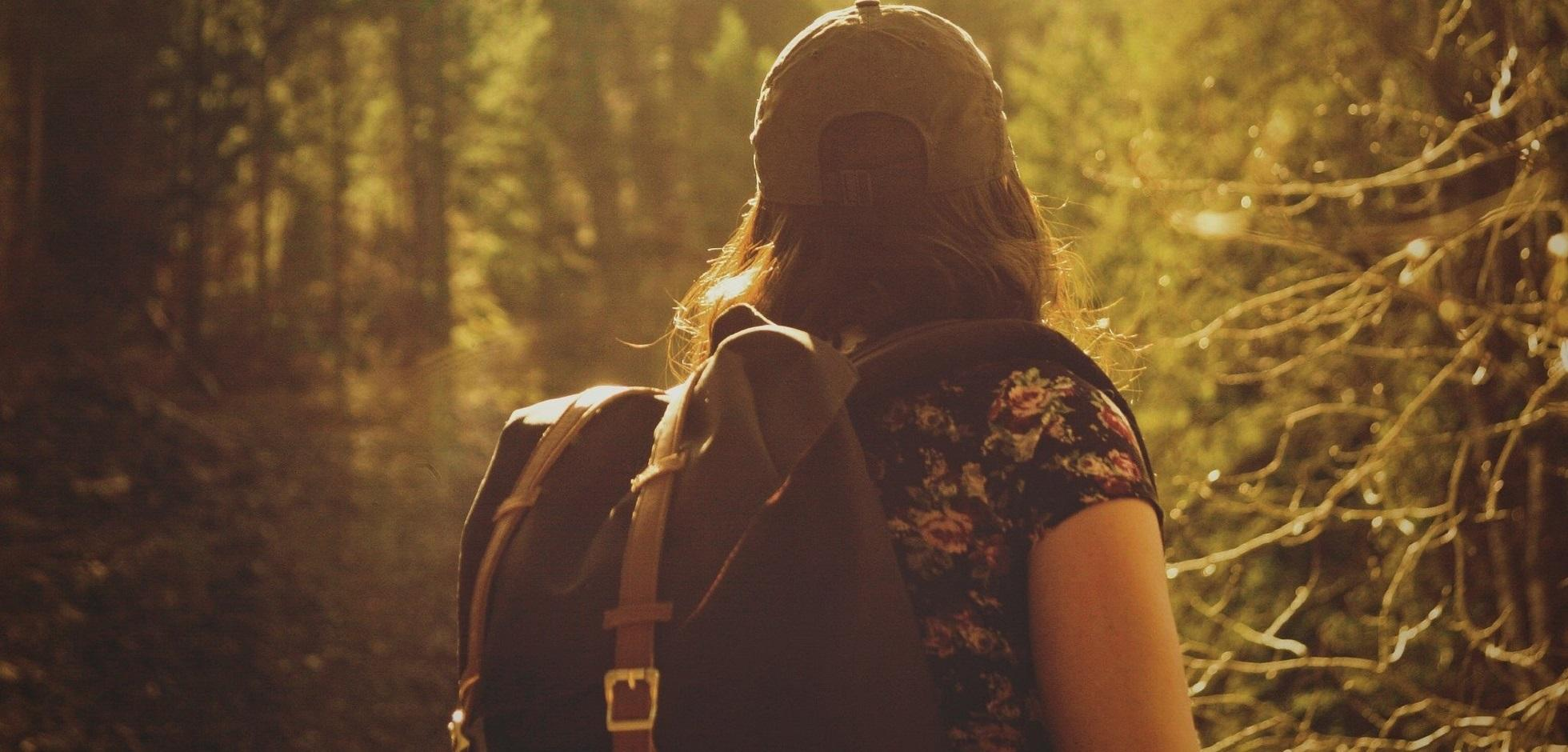 A female with a backpack hiking in a forest