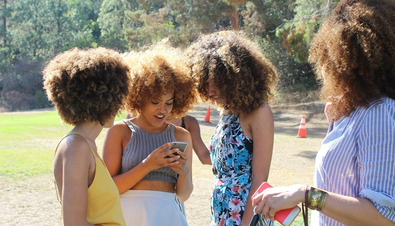 Four young women in a park, laughing and looking at a cellphone