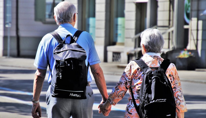 The backs of an elderly couple, a man and a woman, walking on a city sidewalk, holding hands and wearing backpacks