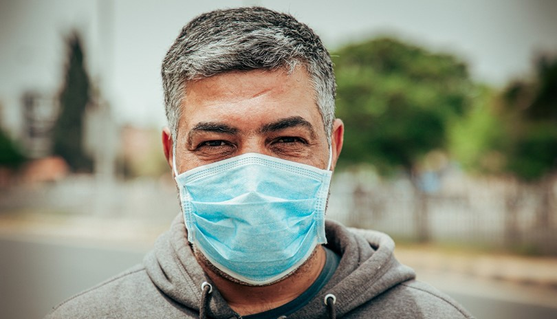 Middle-aged man wearing a non-surgical face mask looking directly into the camera
